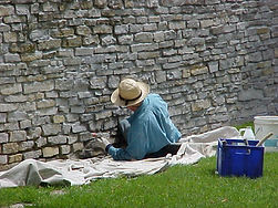 Worker repairing deteriorated limestone.