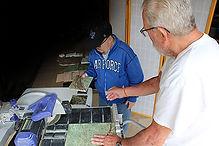 Bob handing Rob stone slab at cutter.jpg