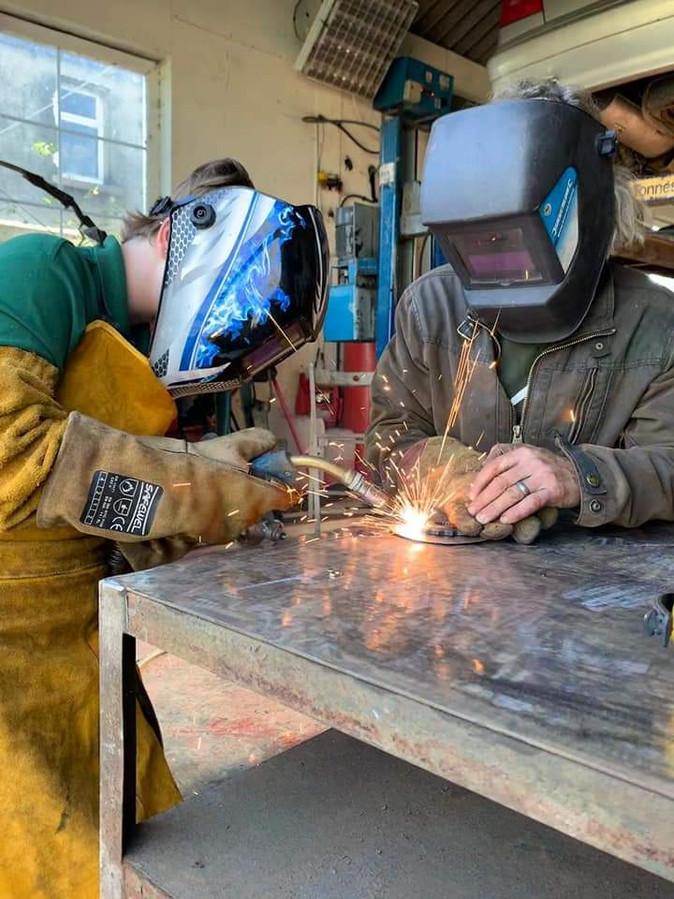 Children creating pieces of art from scrap metal
