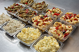 Assortment of side salads including egg, tortellini, pesto, and chicken salad