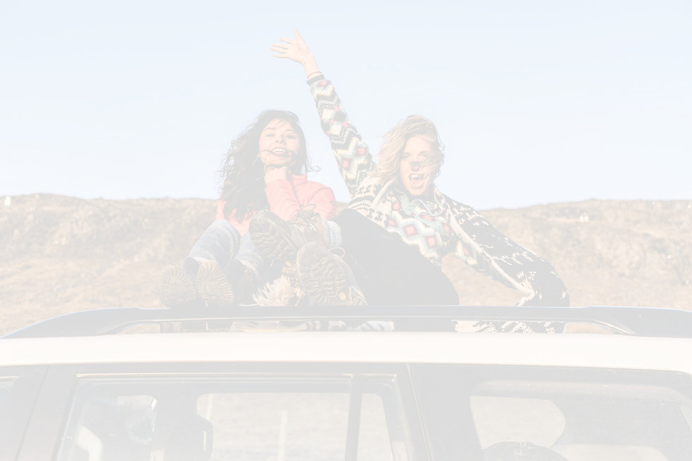 two woman sitting on top of white vehicle under blue sky during daytime_edited_edited.jpg