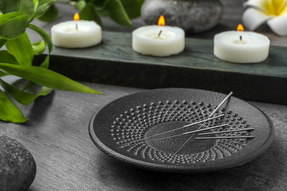Plate with acupuncture needles on table.