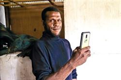 Agunity farmer with phone in Kenya