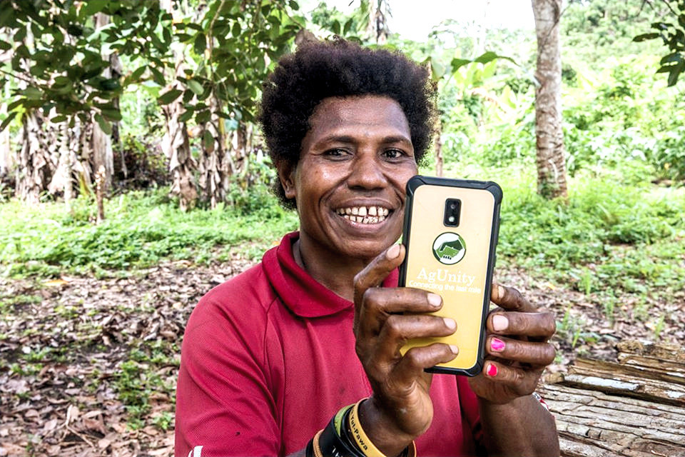 Agunity farmer with phone PNG