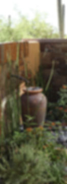 wall fountain with antique spigot and tall brown urn and horsetail reeds