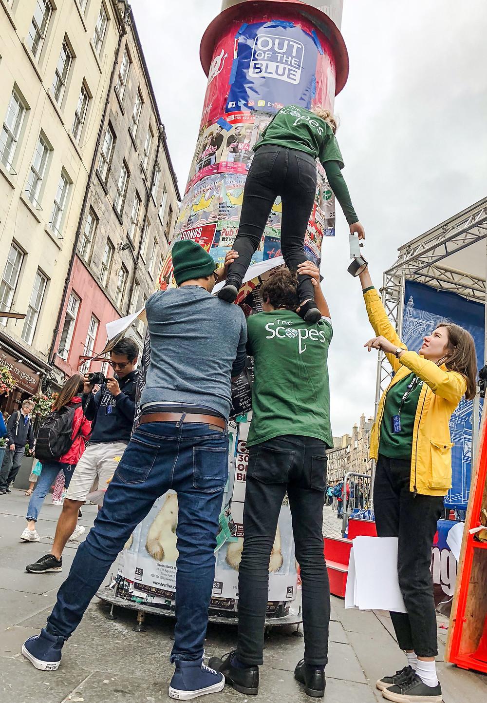 為求突出宣傳效果,工作人員不惜冒險攀爬高處張貼海報,十分落力。