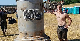 Bryce Boepple standing in front of Warrior Dash sign