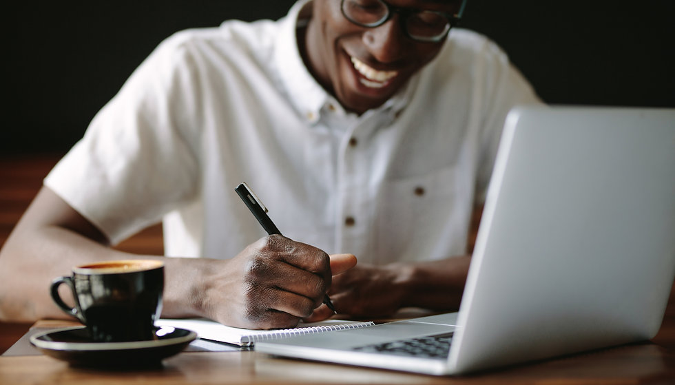 Man Writing Notes Sitting at a Coffee Sh