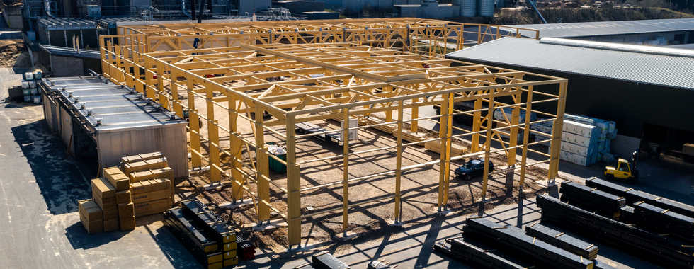Holzhallenbau, Fachwerkträger, Lagerhalle, Balkenlage, Flachdach Tragschale, PIR Wandpaneele Sandwichplatten, lichtfirst Tageslicht, Betonstützen, Transport