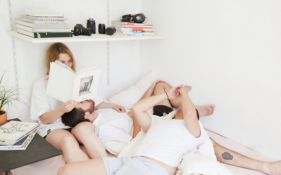 Image of three people laying in bed