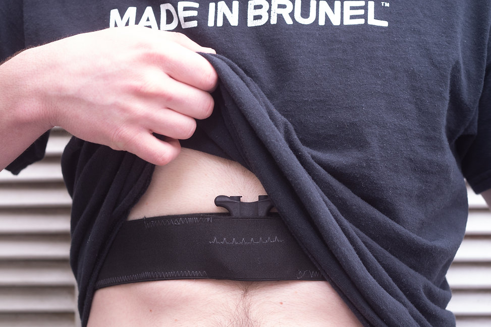 Image of a man lifting up a black tshirt and a strap around his stomach