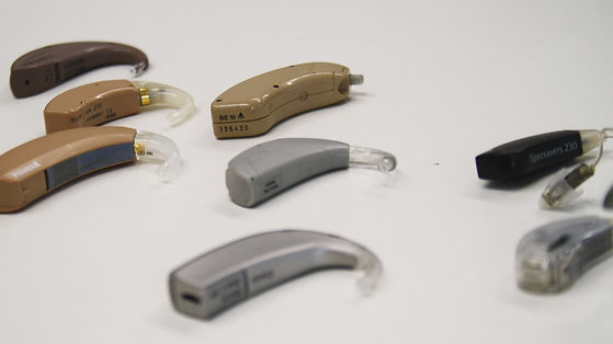 Image of several hearing aids in different colours and sizes