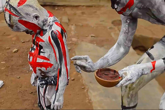 Image of a small child and a man covered in grey, black and red paint