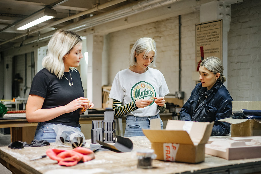 3 students speaking around a workbench in a studio