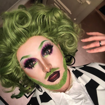 Image of a drag queen with green hair and a green beard