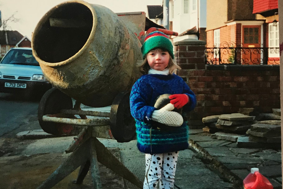 A young girl standing infront of a cement mixer