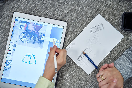 Image of two hands drawing on paper and on a tablet