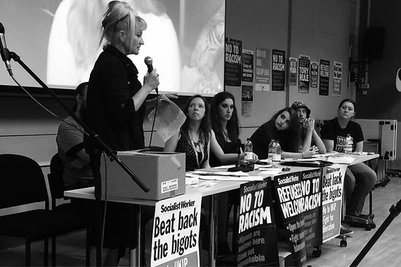 Several people sitting at a desk covered in black and white posters