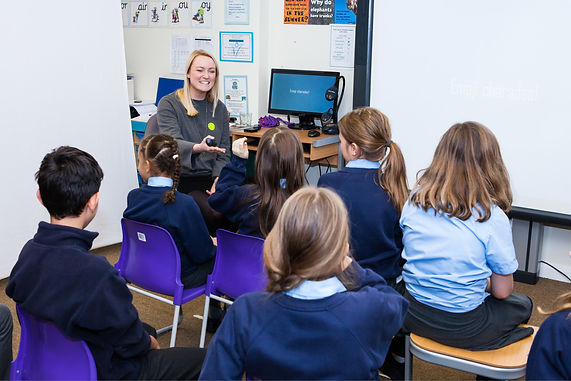 Several school children being taught in a classroom