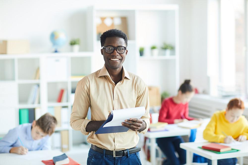 Professor em sala de aula, ele segura uma prancheta na mão e sorri para a câmera. Há três alunos ao fundo. O professor usa uma blusa social e usa óculos.
