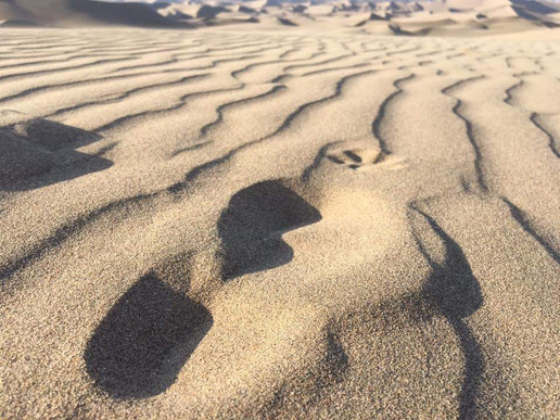 Footprints before sand dune surfing in Huacachina, Peru