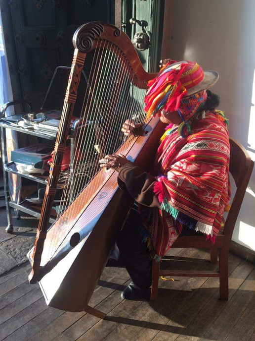 An indigenous musician catching the light in Cusco, Peru