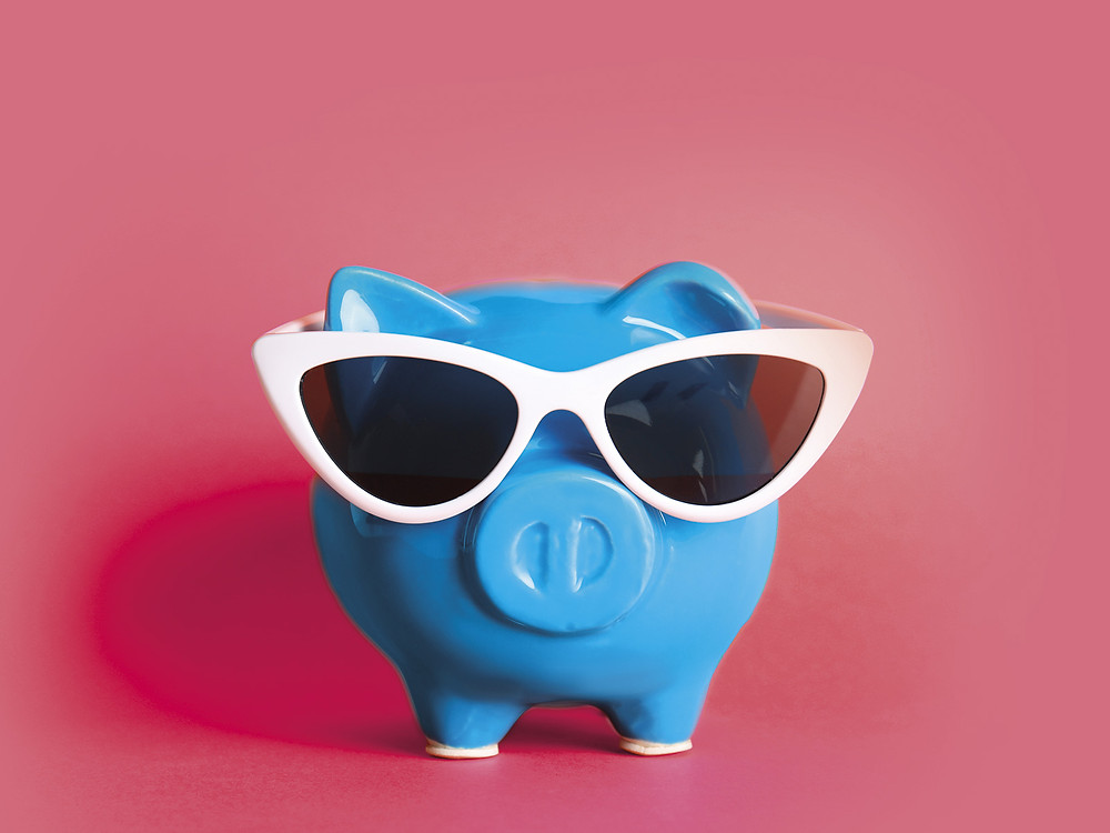 Saving for holidays, illustration of a piggy bank with sunglasses on a pink background