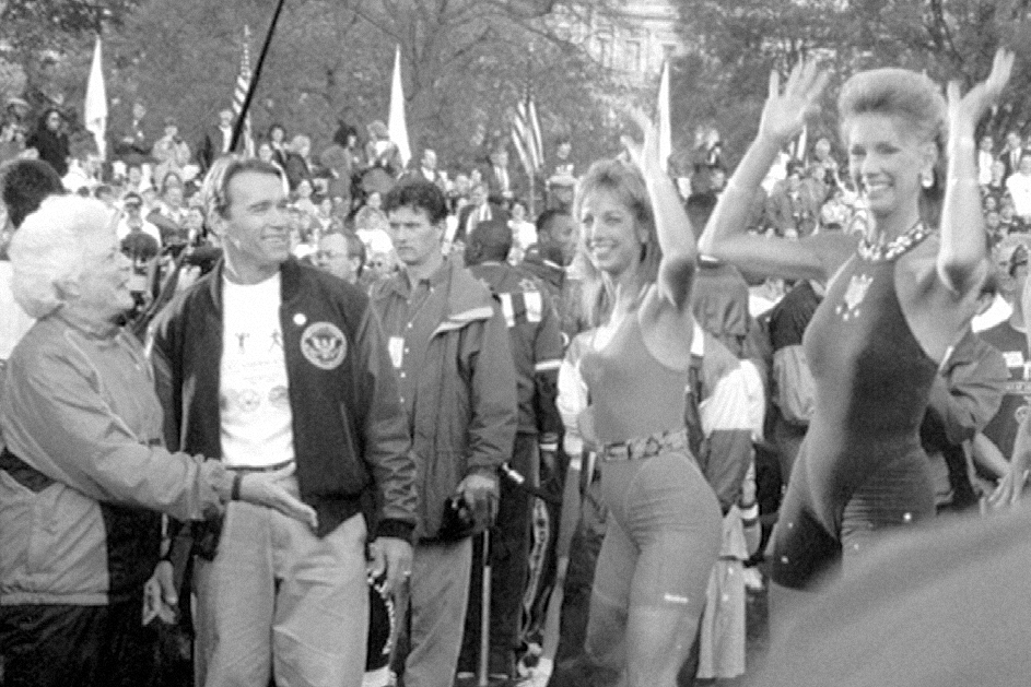 """1991, President George Bush and Arnold Schwarzenegger invite Judi to participate in the """"Great American Workout"""" at the White House"""