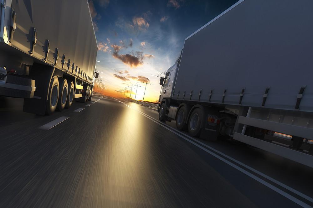 Caminhões na estrada à caminho do crossdock para o varejos entregas e abastecer o varejo.