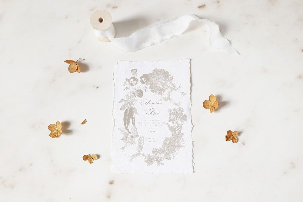Wedding invitation with illustrated floral wreath, printed on handmade paper. The botanical elements included within the wreath illustration are hand picked by the couple and symbolise details of the wedding and the couple.