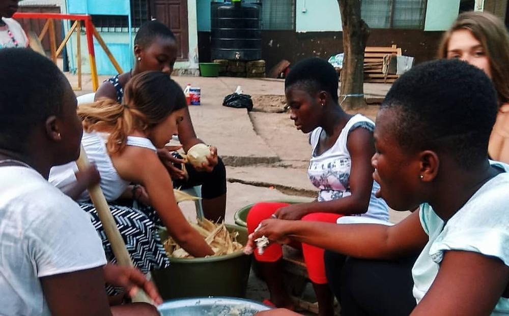 Kids with volunteers preparing kenkey