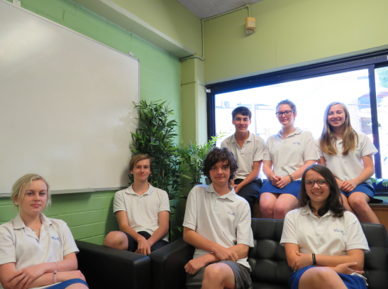 This image contains seven beautiful Colo High kids seated in a pleasant sunny classroom.