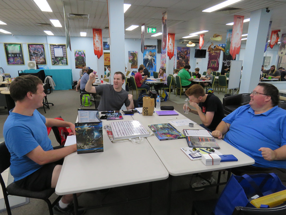 Four men sit at a table of Starfinder books, dice, a gridded board and figurines. The man at the rear of the table brandishes his hand in the air while saying something funny, while the other three men laugh.