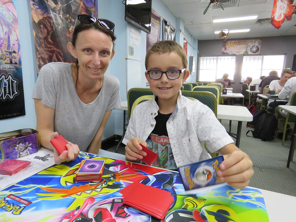 A mother wearing a grey t-shirt is seated at a table with her son, who wears blue framed glasses and a white spotted button-up shirt over a black tee. They are both smiling, and showing off the colourful Pokemon cards and playing mat.