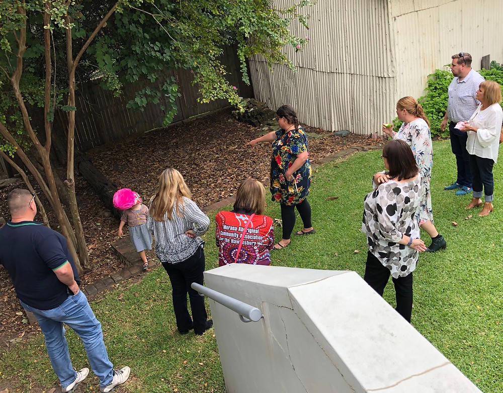 Eight adults and a preschool-aged girl stand in a group on the lawn of the Museum's rear entrance, looking into a garden bed below a macadamia tree. Kath points to the ground below the tree, talking to the group.