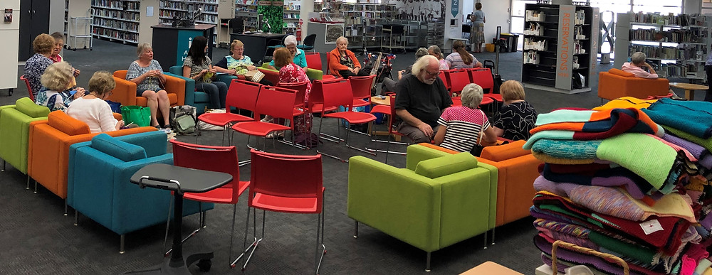 A group of around 15 people are seating in colourful armchairs, knitting and chatting.