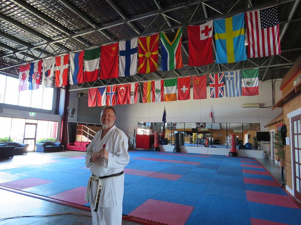 Sensei Daniel Spice at his Richmond dojo, displaying his beautiful array of international flags.