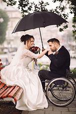 Bride and groom on the wheelchair sit ki