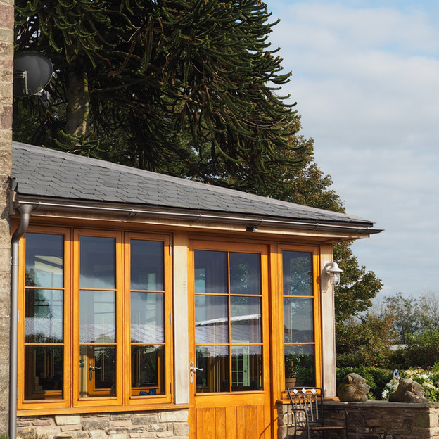 Green oak framed conservatory with chestnut windows and doors