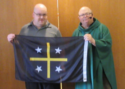 Our Founder with our flag and Fr. Greg.