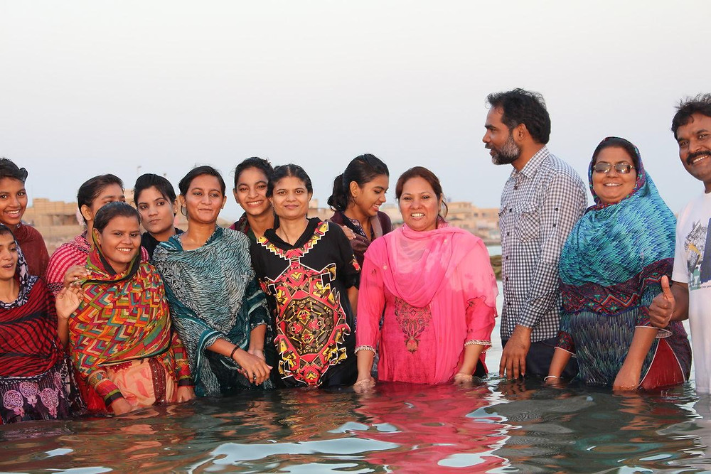 Mushdaq (checkered shirt) and Kanwel (beside him in pink) baptize women who have recently come to faith in Jesus Christ.