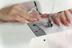 person-sewing-with-a-white-sewing-machin