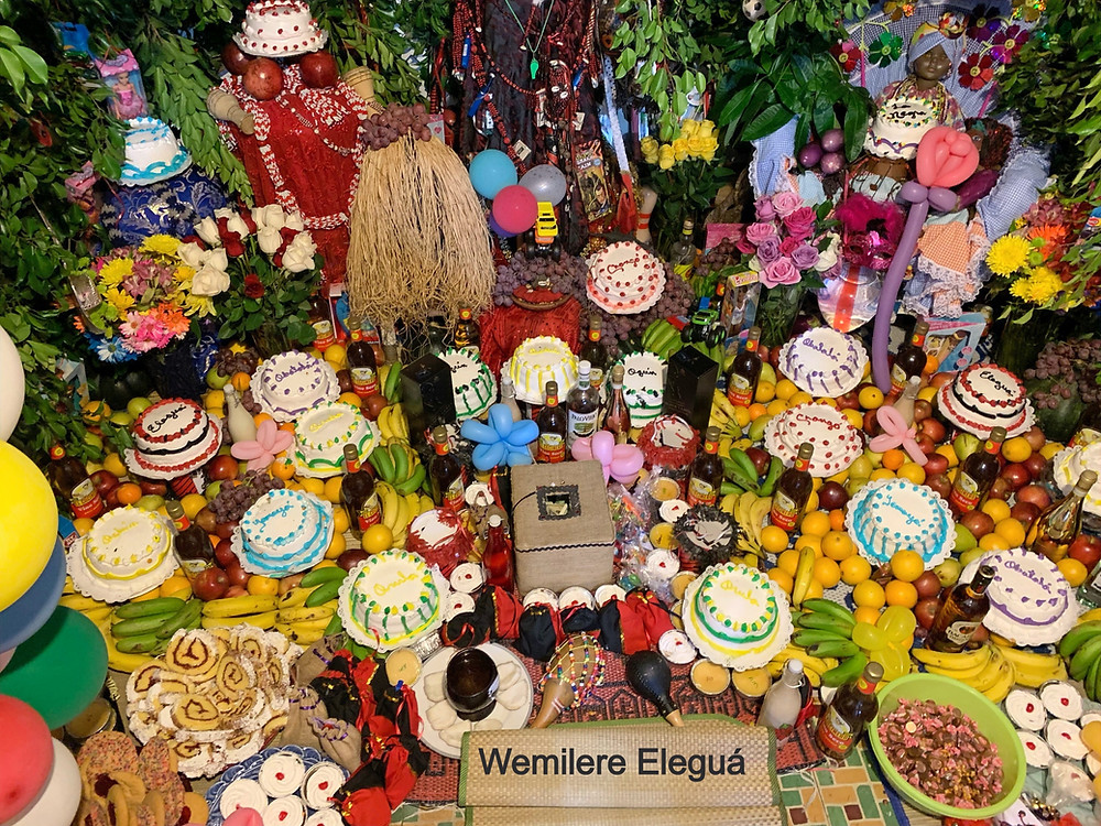 Eleguá surrounded by cakes, candies, toys and fruits.