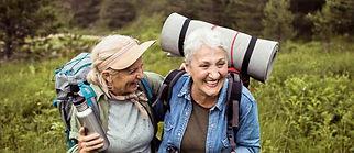 Zwei alte Freundinnen haben Spaß beim Wandern und lachen