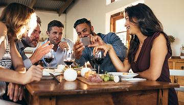 Freunde essen gemeinsam am Tisch und schießen ein Selfie Foto