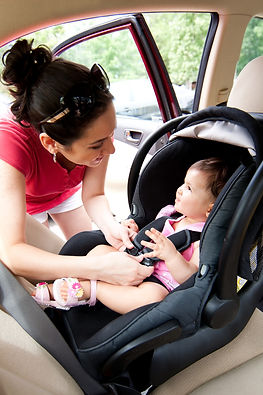 Woman putting baby into a car seat.