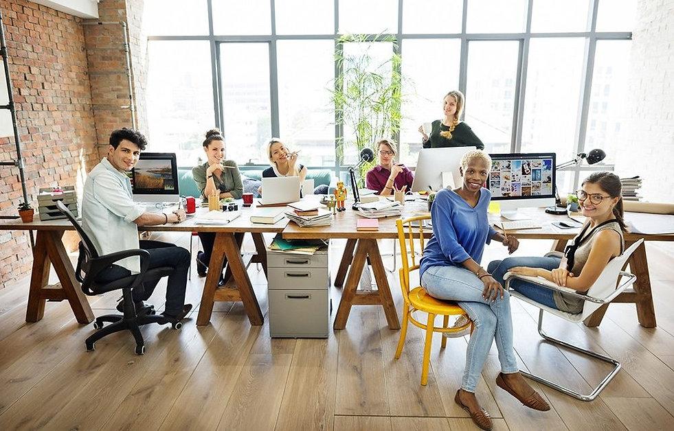 Mesa de trabalho com sete colaboradores sorrindo de forma descontraída olhando para câmera