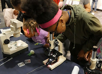 A young student looking into a microscope at a museum.