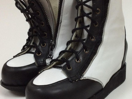 Black and white boots that zip up on both sides of the boot