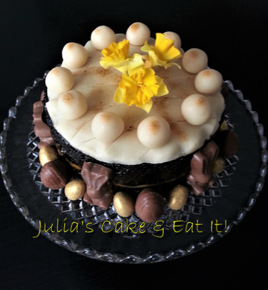 Bury Simnel Cake - rich fruit cake with a layer of marzipan in the middle.  Top decorated with eleven marzipan balls to represent the apostles, minus Judas, and handmade sugar daffodils